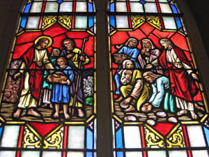 The stained glass windows in the nave pair New Testament scenes with those in the Old Testament that prefigure them. Here we see, on the left the New Testament multiplication of the loaves and fish and Bread of Life discourse paired with the Old Testament story of the Manna in the desert.